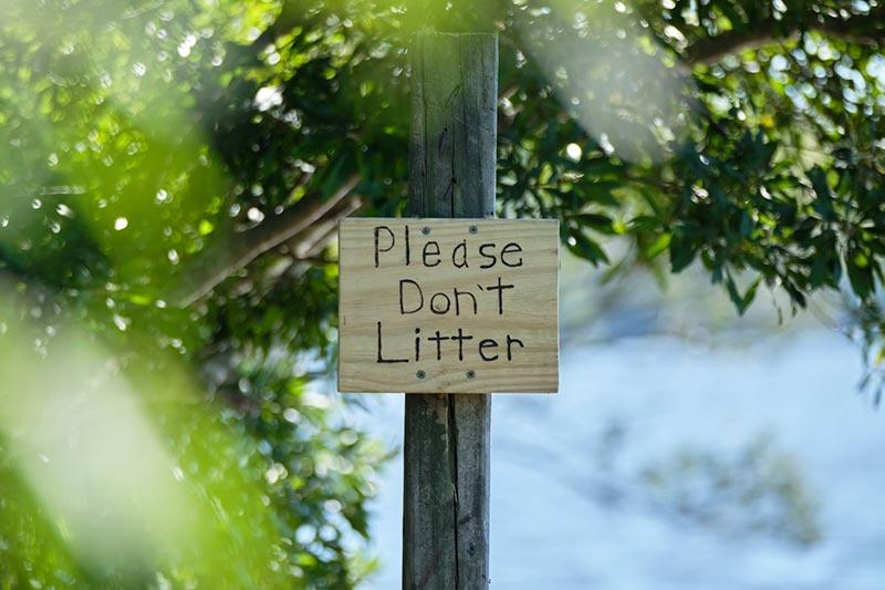 """Schild mit der Aufschrift """"Please don't litter"""""""
