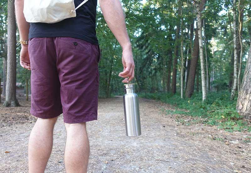 Mann mit Trinkflasche aus Edelstahl, der Leitungswasser trinkt