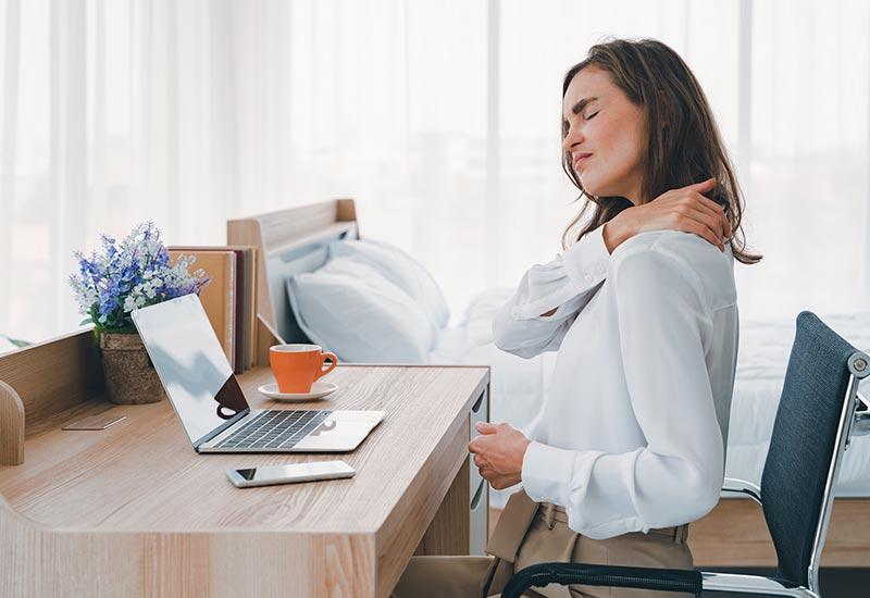 Junge Frau mit Nackenschmerzen im Büro