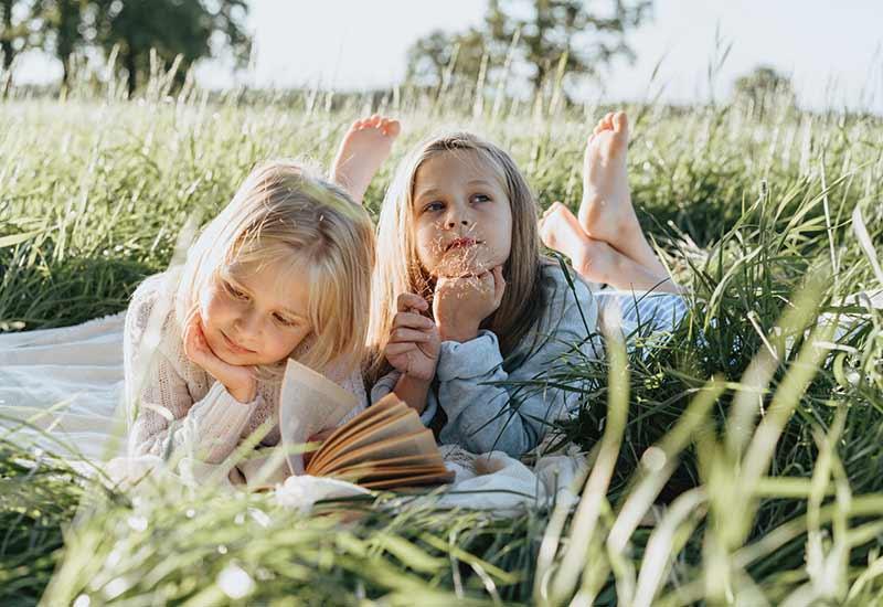 Zwei Mädchen lesen Bücher an der frischen Luft
