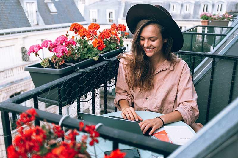 Frau arbeitet auf dem Balkon am Laptop