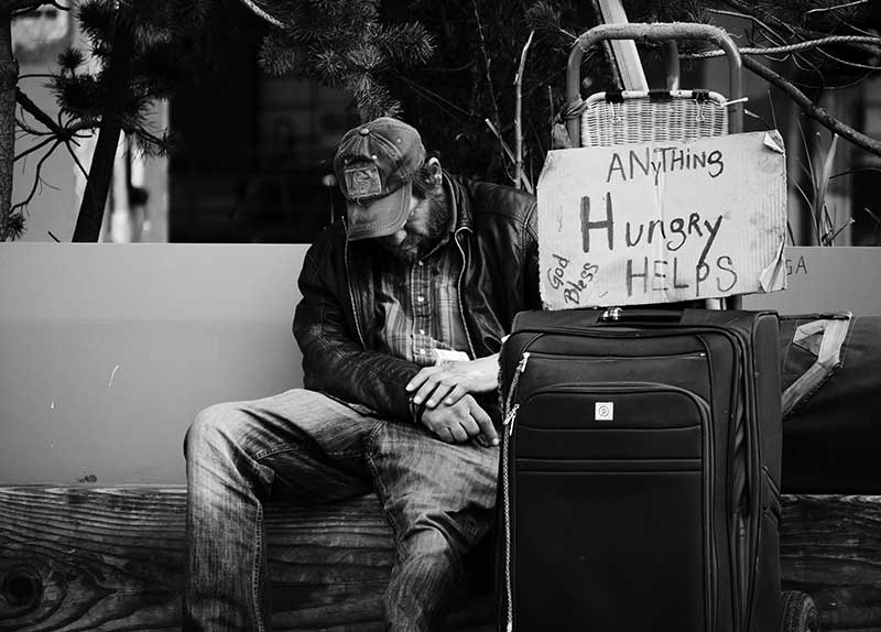 Hungriger Bettler auf Bank