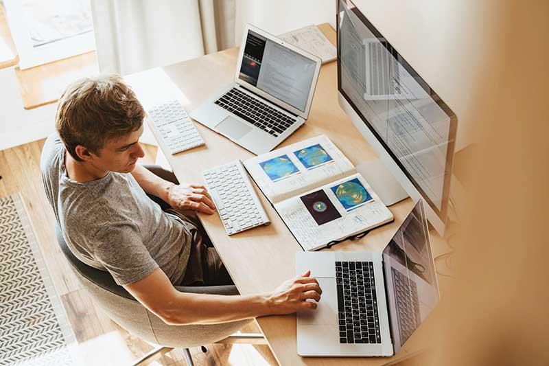 Mann arbeiten im Homeoffice mit drei Computern