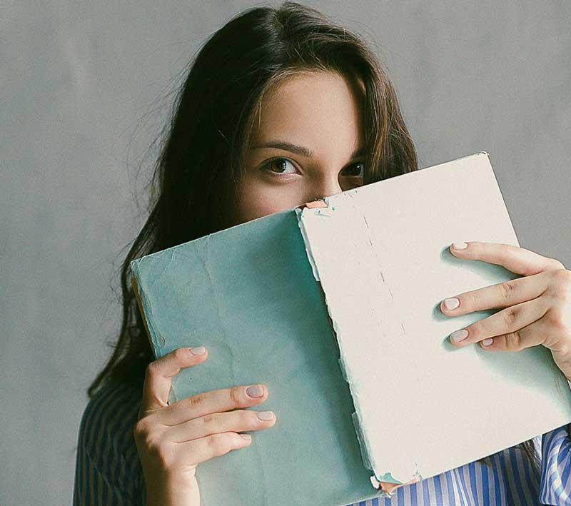 Frau schaut über ein Buch