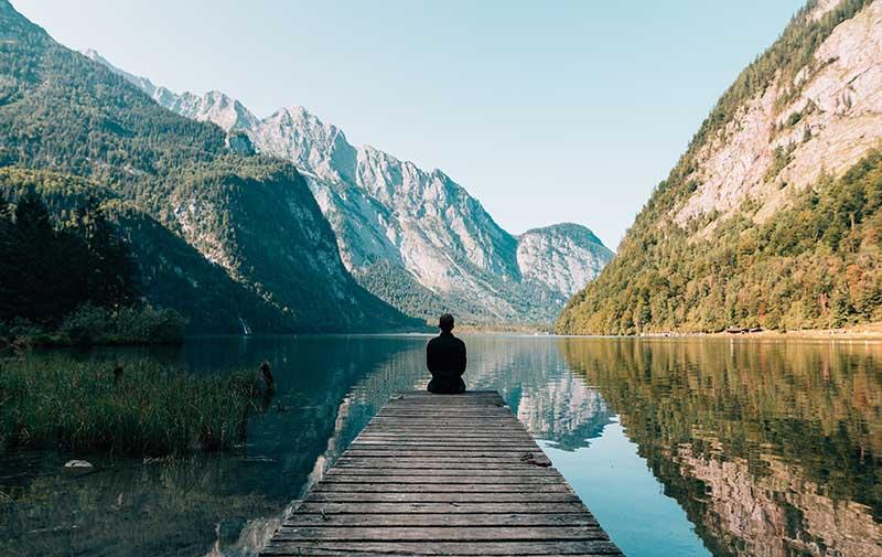 Mann auf Steg in Berg und Seenlandschaft